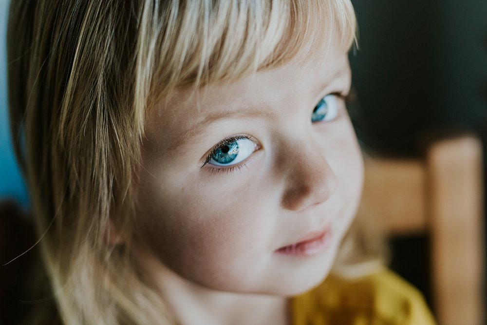 Orange County family photographer. Portrait of beautiful four year old girl in mustard dress and big blue eyes taken during in home family session in Long Beach