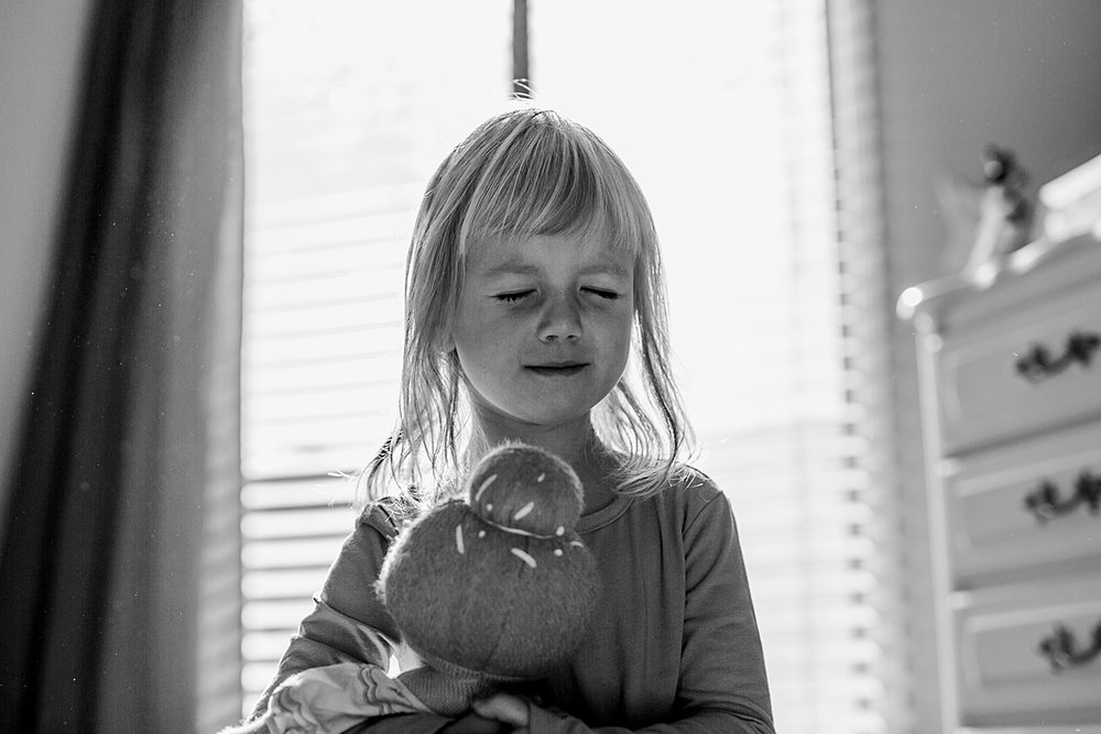 Orange County family photographer. Candid portrait of four year old girl as she holds her stuffed toy in her room squishing her eyes closed taken during in home family session in Long Beach