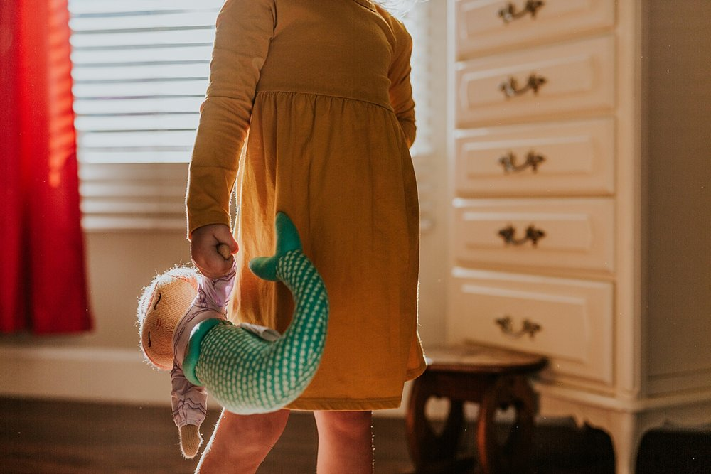Orange County family photographer. Portrait of beautiful four year old girl in mustard dress clutching her mermaid toy in her room during in home family session in Long Beach