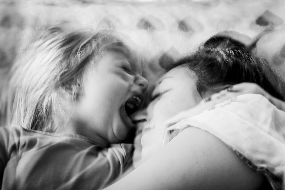 Orange County family photographer. Double exposure photo of mom and daughter playing on daughter's bed taken during in home family photo session in Long Beach, CA