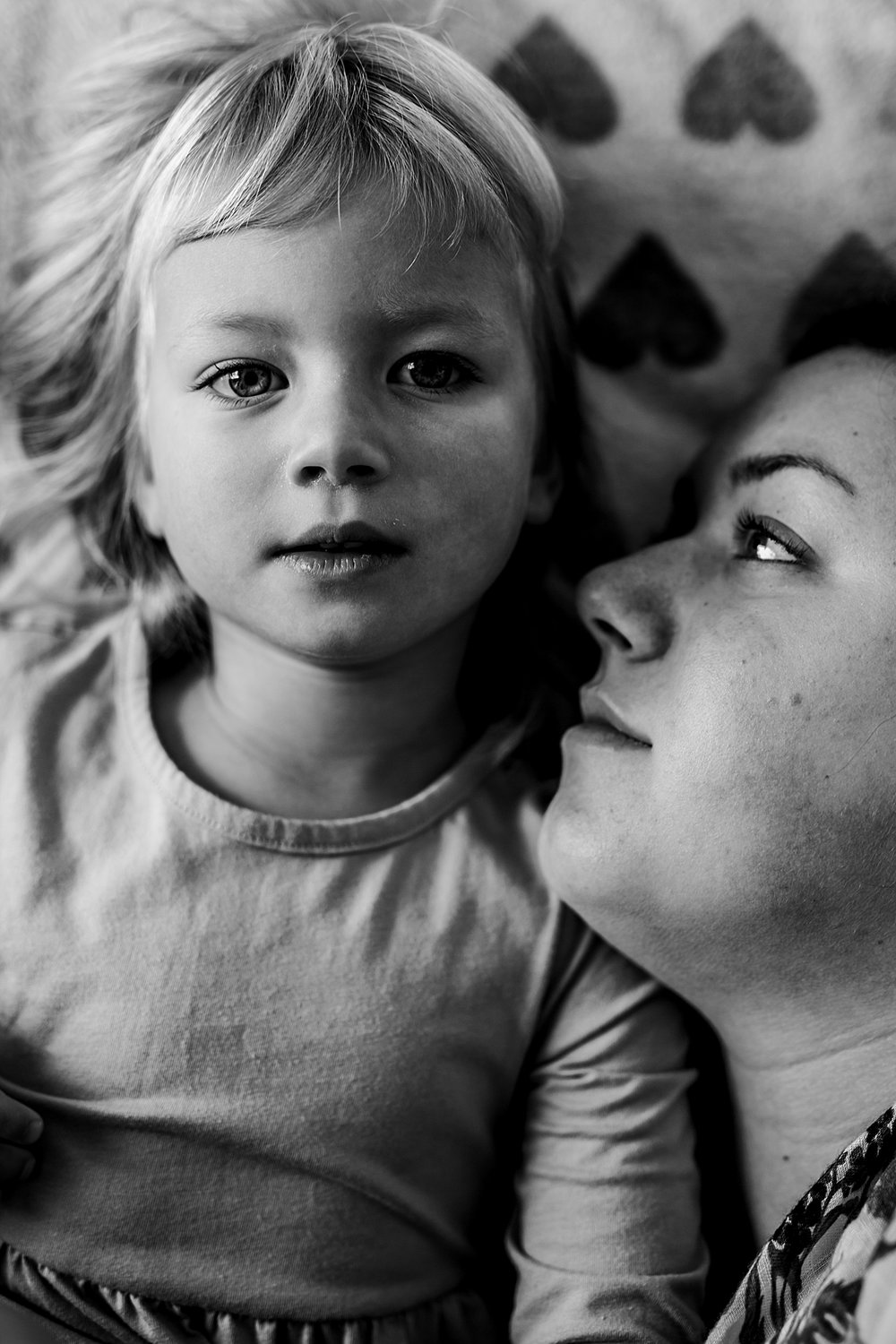 Orange County family photographer. Black and white photo of mom and daughter taken while laying flat on daughter's bed during in home family photo session in Long Beach, CA