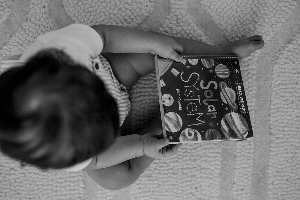 Orange County family photographer. Photo from above of 1 year old boy holding a kids book during in family photo session in Irvine CA