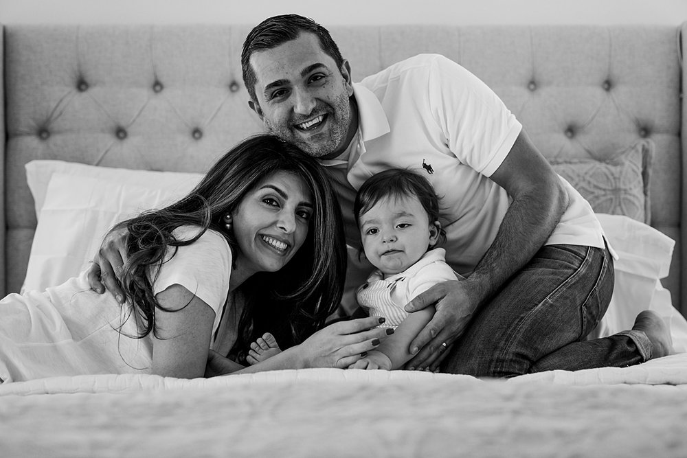 Orange County family photographer. Photo of mom, dad and son posing on bed during family photo session in Irvine CA