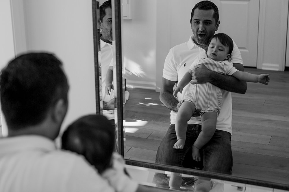 Orange County family photographer. Candid photo of dad and son playing together as they look in the mirror during family photo session in Irvine CA