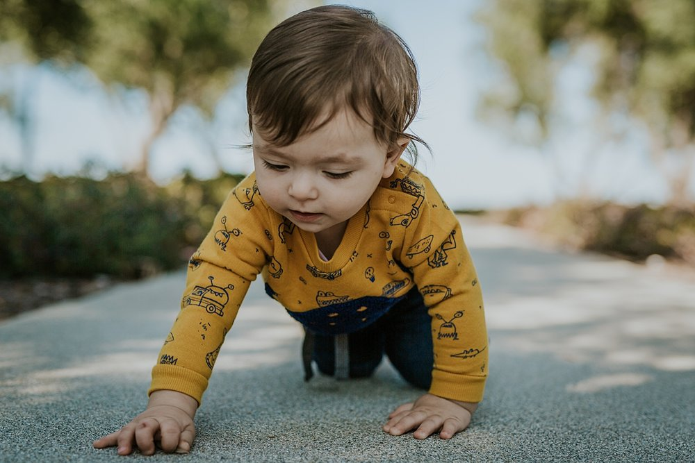 Orange County family photographer. Candid photo of one year old boy crawling across local part footpath during family photo session in Irvine CA