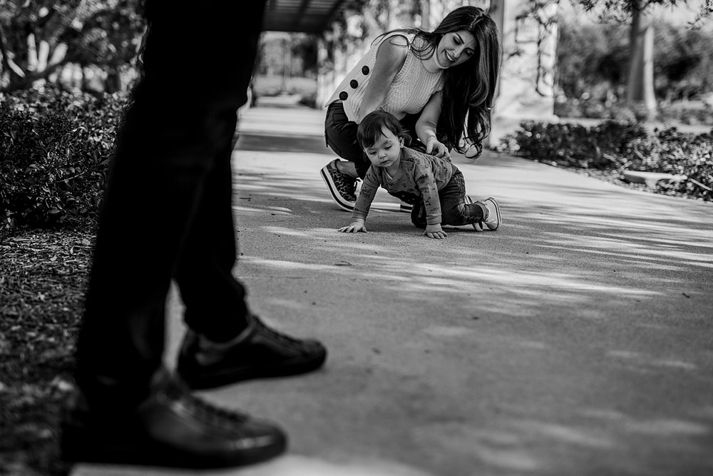 Orange County family photographer. Candid photo of one year old boy crawling towards dad's shoes at local Irvine park during family photo session in Irvine CA