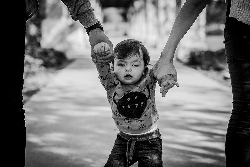 Orange County family photographer. Candid photo of son walking hand-in-hand with his parents at local Irvine park during family photo session in Irvine CA