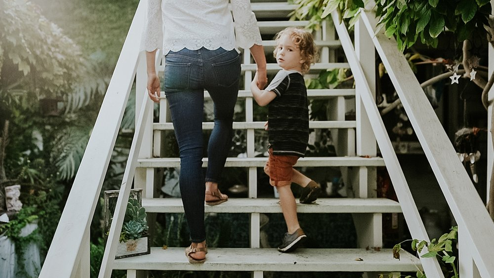 Orange County family photographer. Cute curly blonde haired boy walks up the stairs with his mom during in home session at Huntington Beach