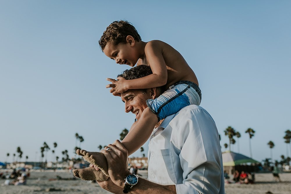 Orange County family photographer. Photo of young boy getting a shoulder ride from his dad at Newport Beach Pier during outdoor family photo beach session