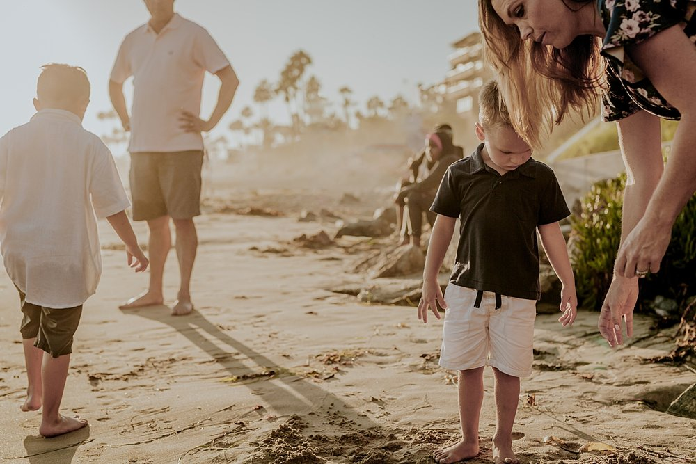 Orange County family photographer. Photo of family of four leaving a day at Big Corona Beach in Orange County