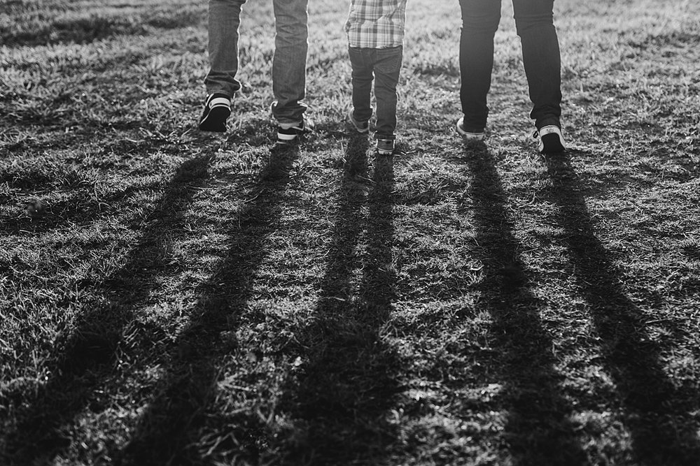 Orange County family photographer. Photo of shadows of family of three as they stand in the sunset during outdoor maternity photo session at Irvine Regional Park