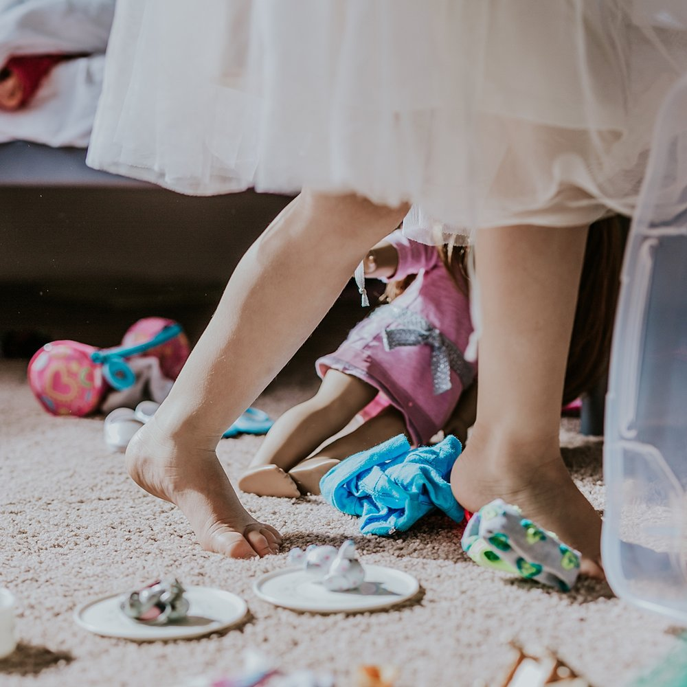 Orange County family photographer. Photo of daughter's feet as she runs across her carpeted bedroom floor wearing a tutu during family photo shoot in Huntington Beach
