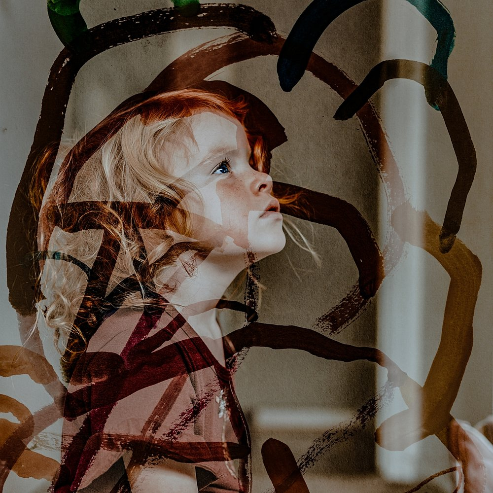 Orange County family photographer. Double exposure photo of sweet  red haired girl with her hand painting overlaid on the top during family photo shoot in Huntington Beach