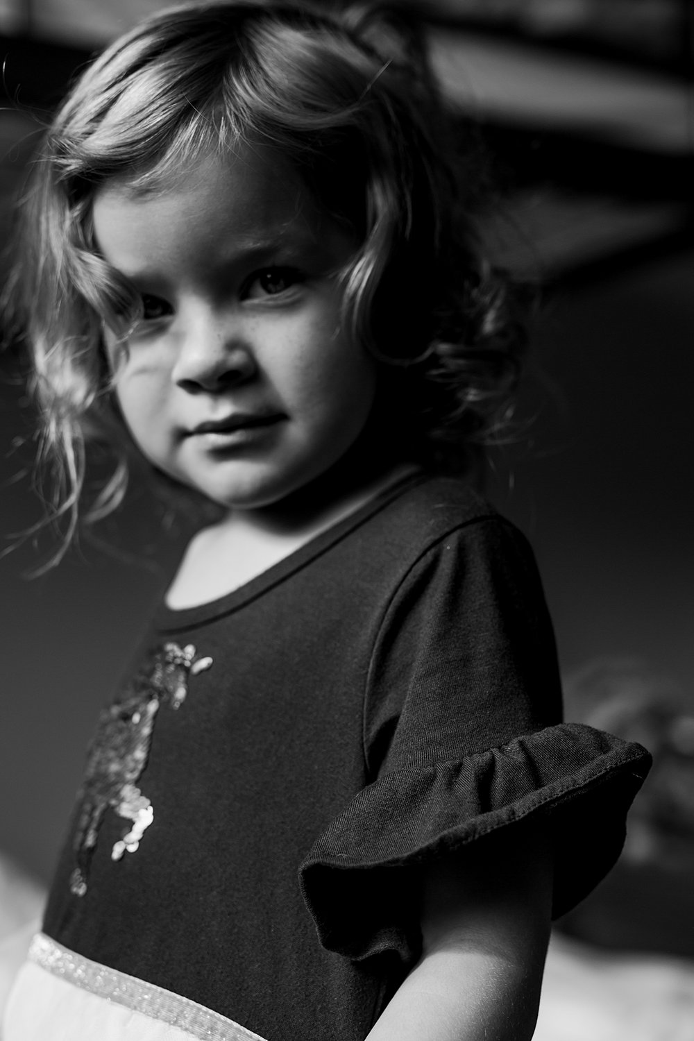Orange County family photographer. Black and white portrait of daughter standing in her room and looking straight at the camera during family photo shoot in Huntington Beach