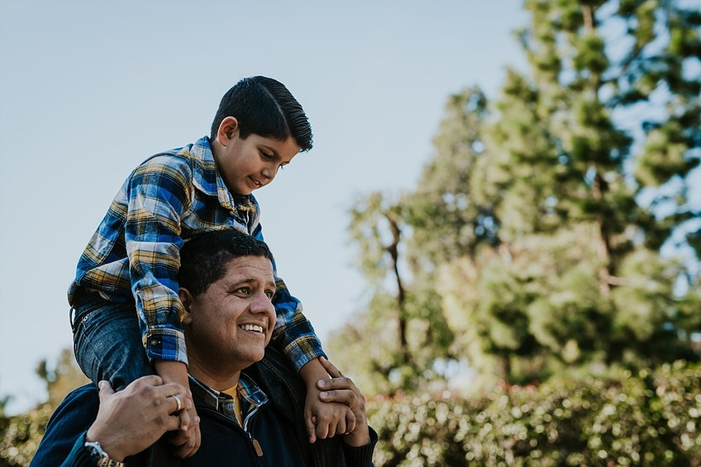 Orange County family photographer. Dad giving his son shoulder ride during family photo shoot at abandoned railway tracks in orange county