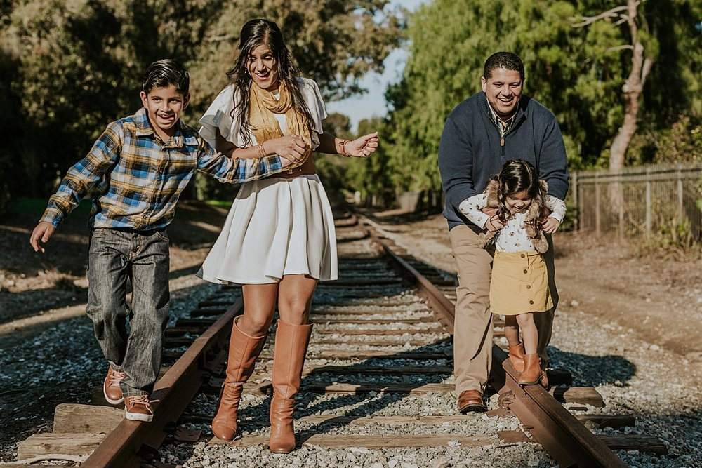 Orange County family photographer. Family of four play on abandoned railway tracks during outdoor family photo shoot in orange county california