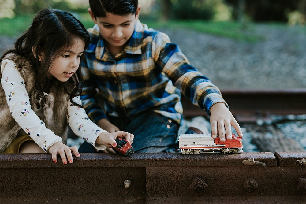 Orange County family photographer. Photo of brother and sister playing with toy trains on abandoned railway tracks during outdoor family photo shoot in orange county california