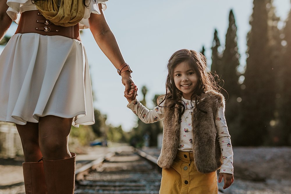 Orange County family photographer. Portrait of daughter holding her mother's hand as they walk along abandoned railway tracks during outdoor family photo shoot in orange county