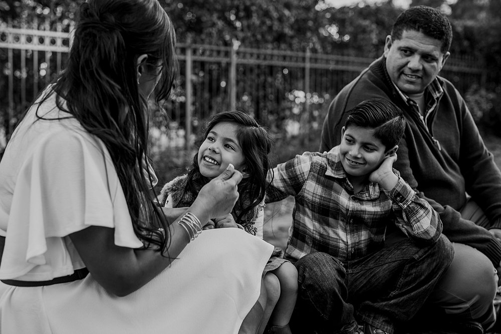 Orange County family photographer. Black and white candid family photo of family sitting on abandoned railway tracks during outdoor family photo shoot in orange county