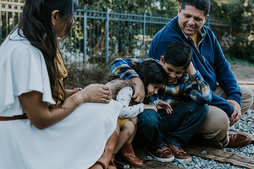 Orange County family photographer. candid family photo of family sitting on abandoned railway tracks during outdoor family photo shoot in orange county
