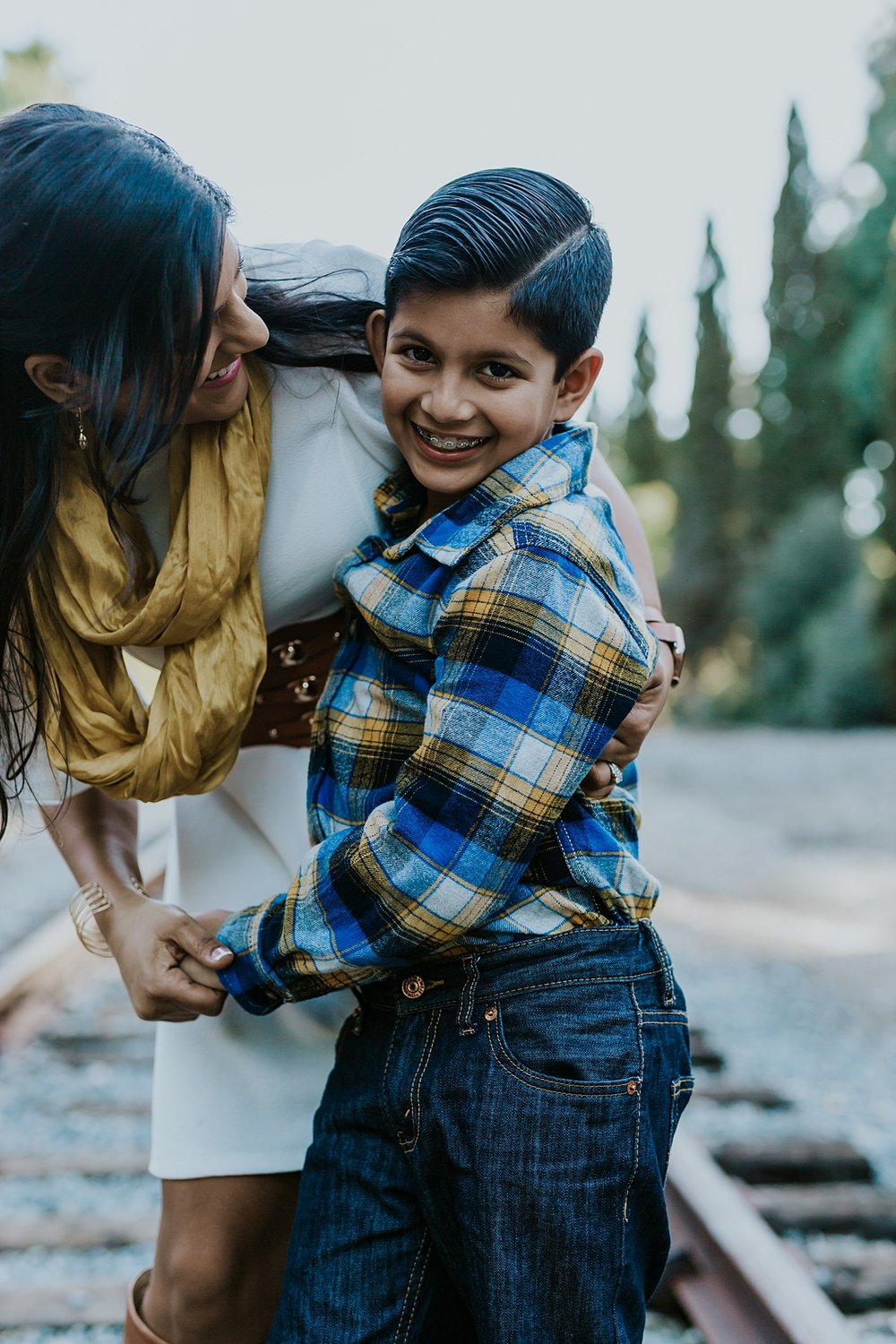 Orange County family photographer. photo of mom and her son laughing as they stand on abandoned railway tracks during outdoor family photo shoot in orange county