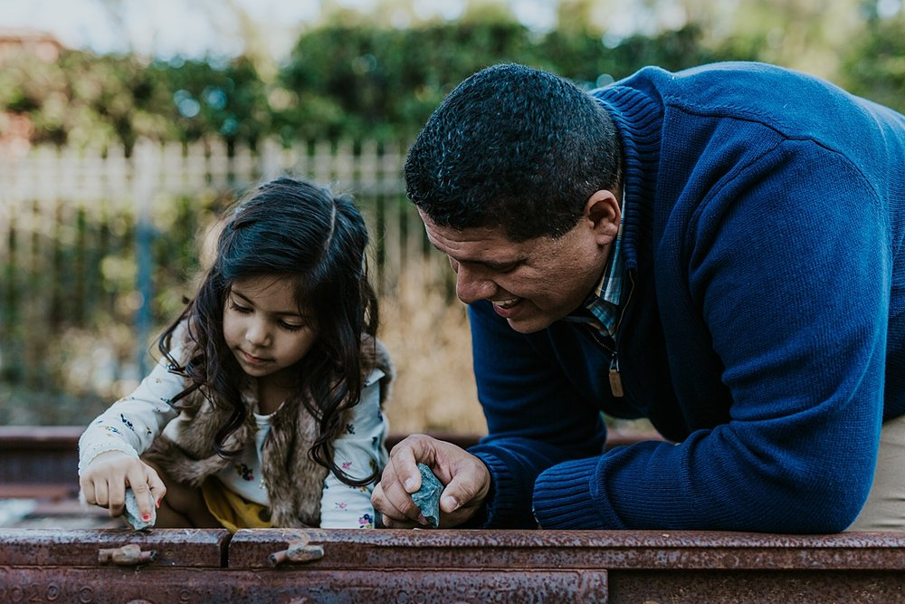 Orange County family photographer. Photo of dad and daughter writing on the train tracks with rocks during outdoor family photo shoot in orange county