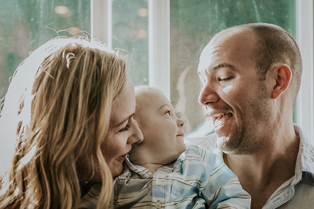 Orange County family photographer. Mom, dad and son sit in front of light drenched window looking cute during in home family photo shoot in Huntington Beach