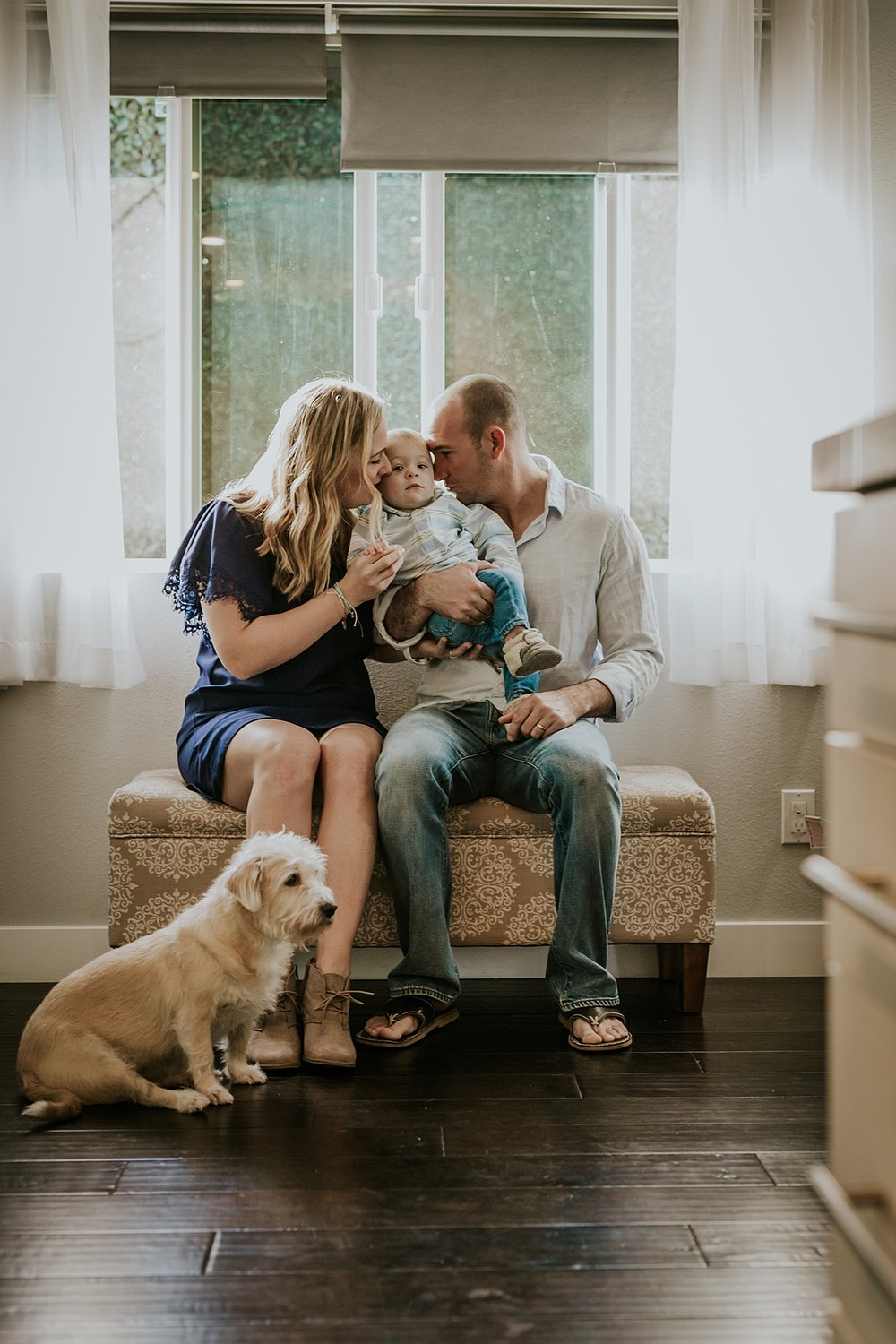 Orange County family photographer. Mom, dad, dog and son sit in front of light drenched window looking cute during in home family photo shoot in Huntington Beach