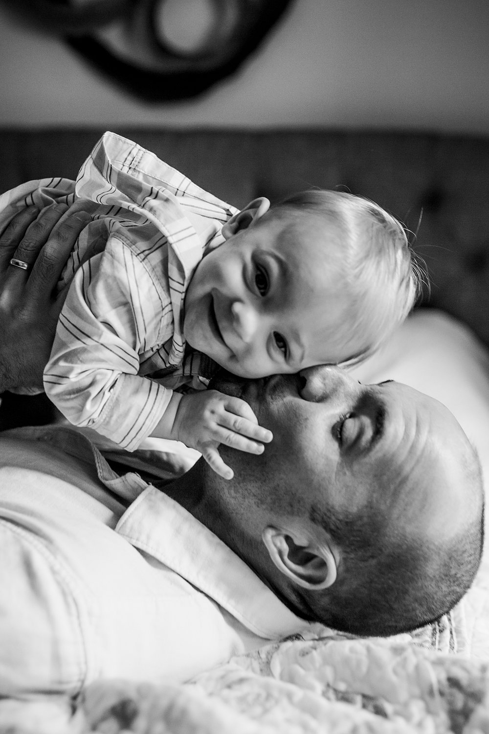 Orange County family photographer. Candid black and white photo of dad and his sweet boy laughing and rolling around on the bed during in home family photo shoot in Huntington Beach