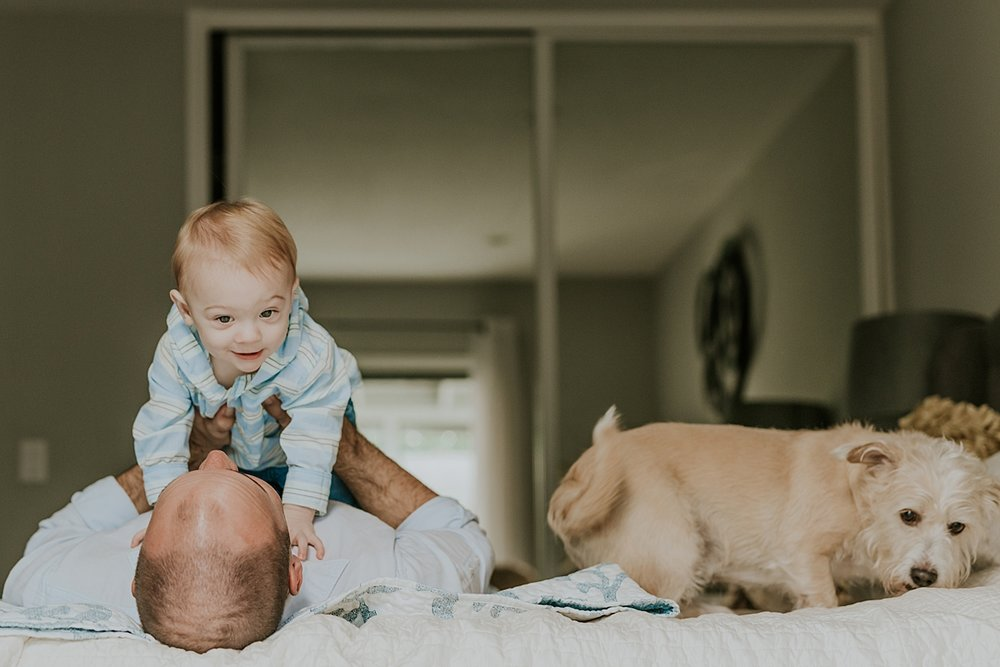 Orange County family photographer. photo of dad, his son and their dog all hanging out on the bed during in home family photo shoot in Huntington Beach