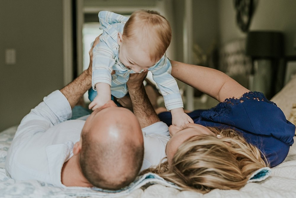 Orange County family photographer. photo of dad, mom and son playing on parent's bed during in home family photo shoot in Huntington Beach