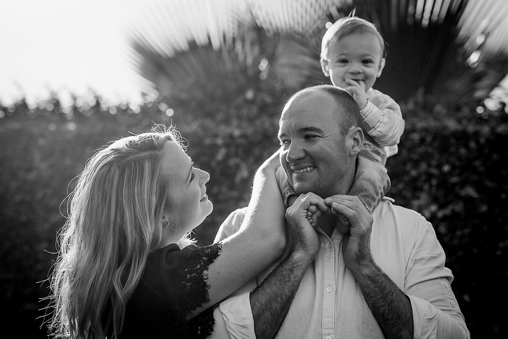 Orange County family photographer. Black and white photo of mom and dad giving son a shoulder ride in the backyard during in home family photo shoot in Huntington Beach