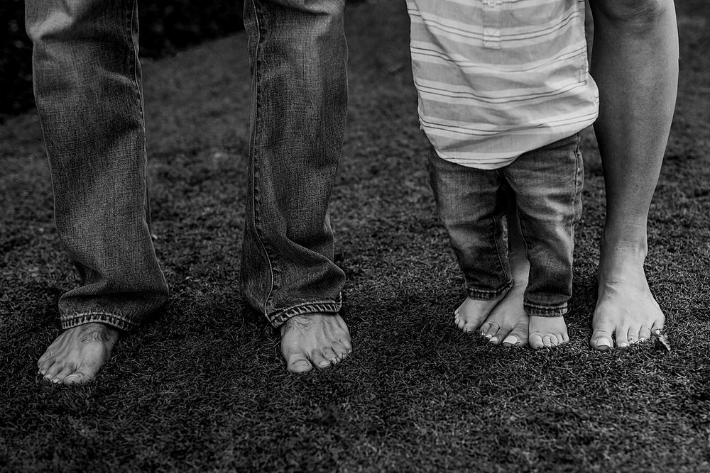 Orange County family photographer. Black and white details photo of mom, dad and boy's bare feet standing in backyard during in home family photo shoot in Huntington Beach