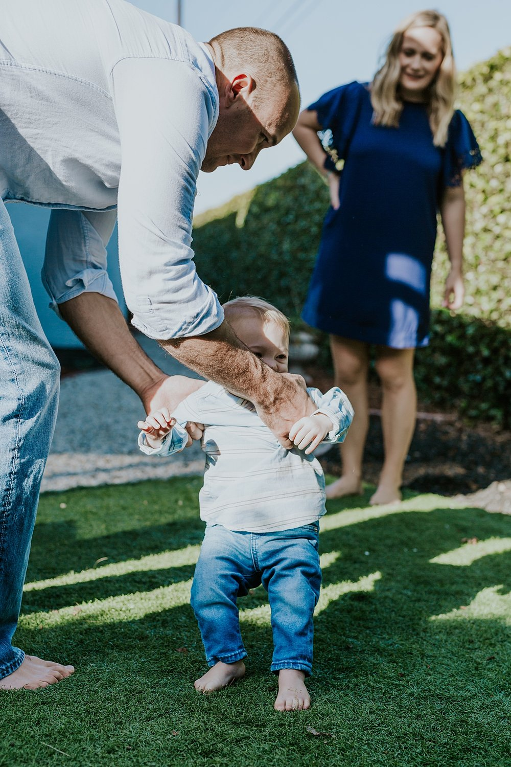 Orange County family photographer. candid photo of dad moving son while mom stands in the background during in home family photo shoot in Huntington Beach