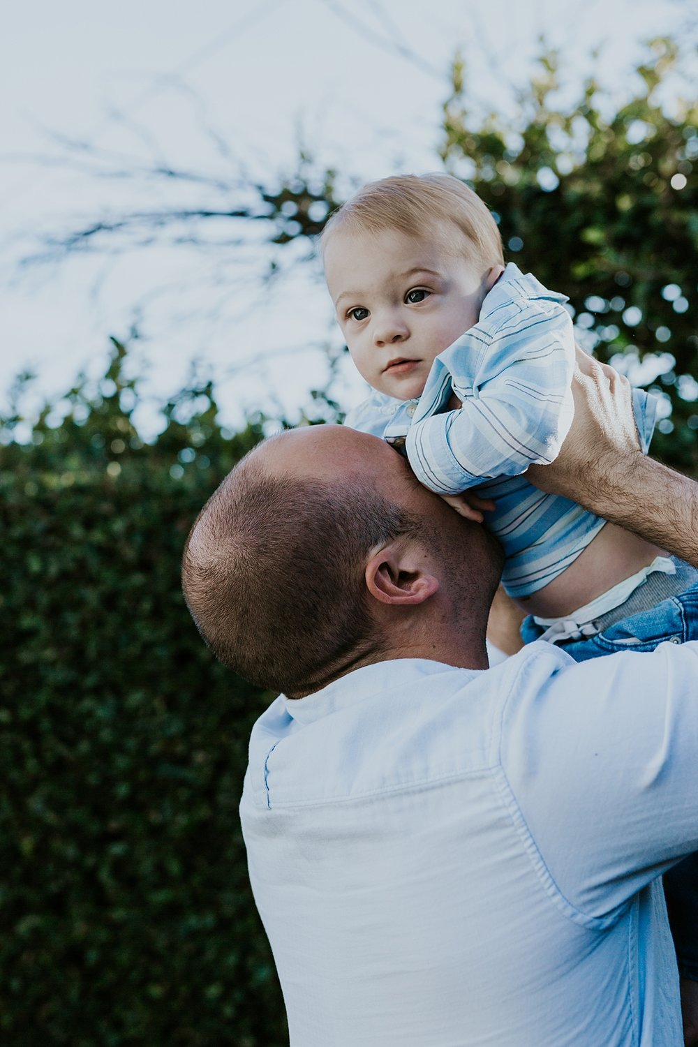 Orange County family photographer. photo of dad snuggling his super cute blonde haired son in their backyard during in home family photo shoot in Huntington Beach
