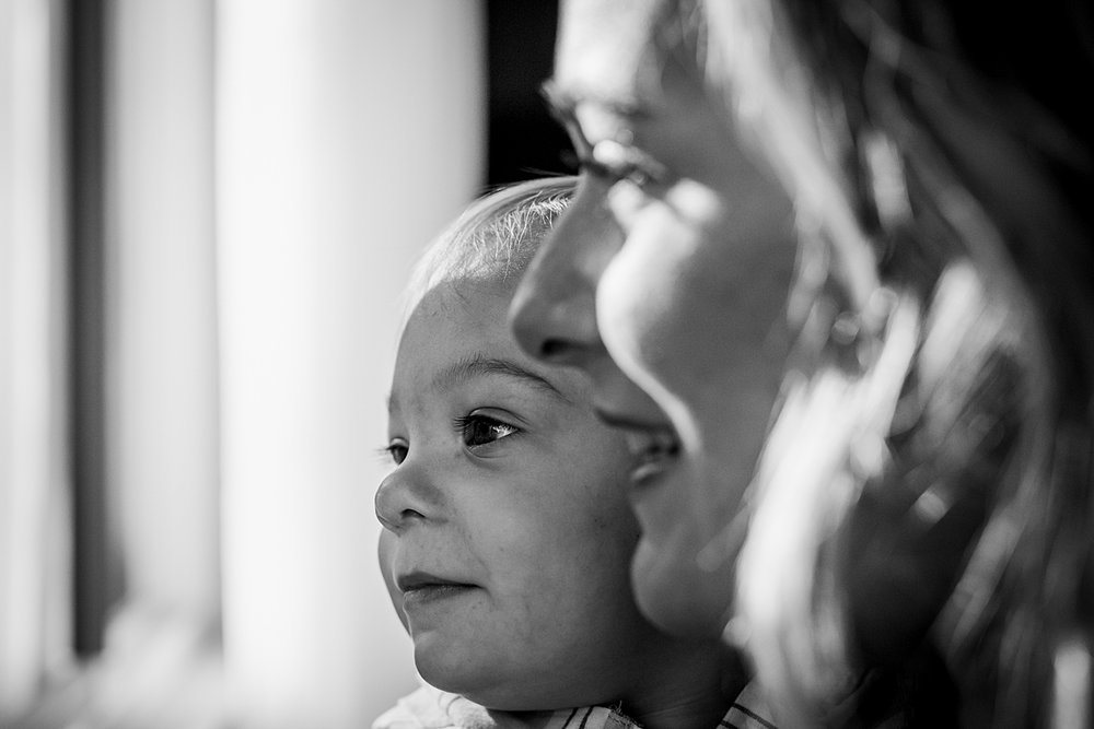 Orange County family photographer. Close up black and white photo of mom and her son looking out the window during in home family photo shoot in Huntington Beach