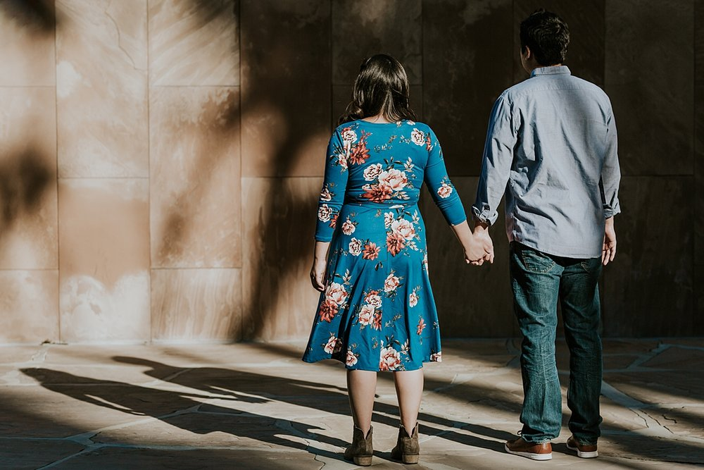 Orange County family photographer. Married couple stands holdings hands and looking at their shadows at sunset during maternity photo shoot at Noguchi Garden Costa Mesa