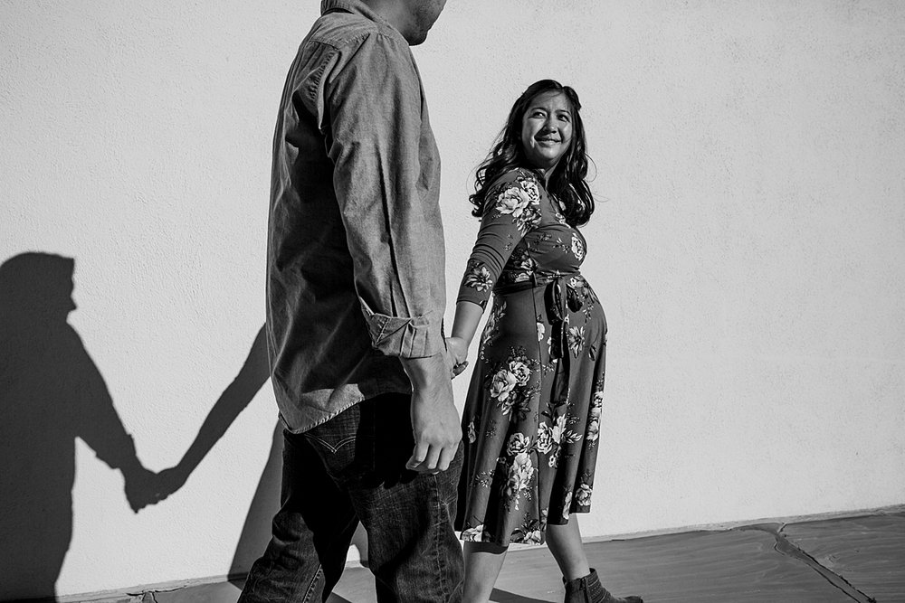Orange County family photographer. Black and white photo of expecting couple hold hands and walk along white wall during maternity photo shoot at Noguchi Garden Costa Mesa