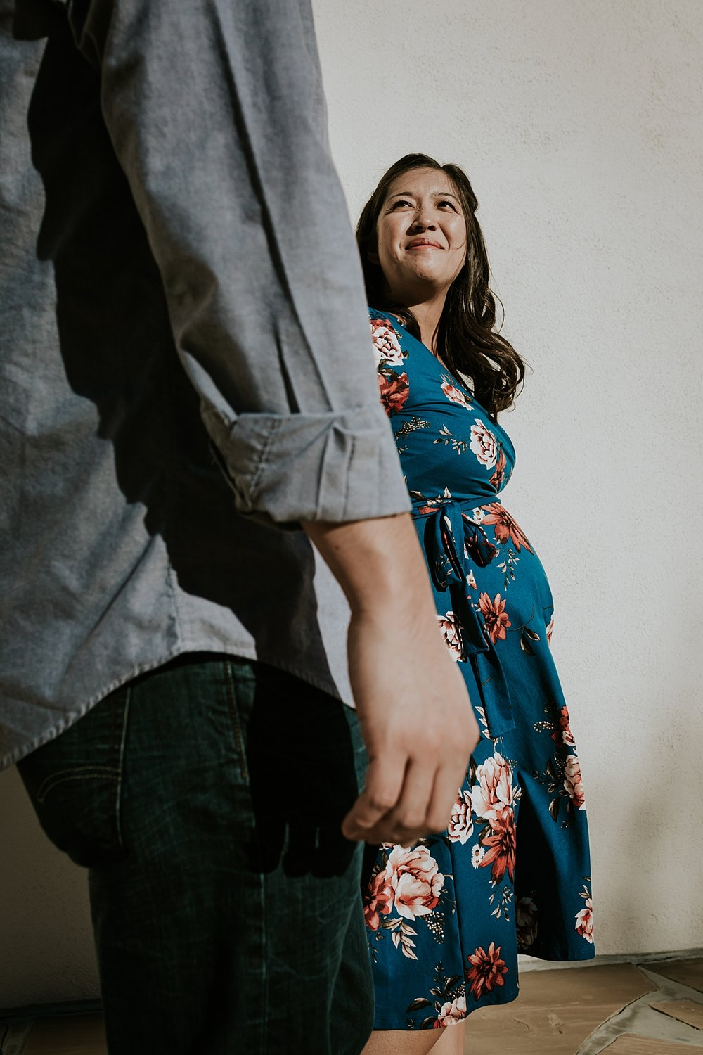 Orange County family photographer. Photo taken from below perspective of couple holding hands and walking together during maternity photo shoot at Noguchi Garden Costa Mesa