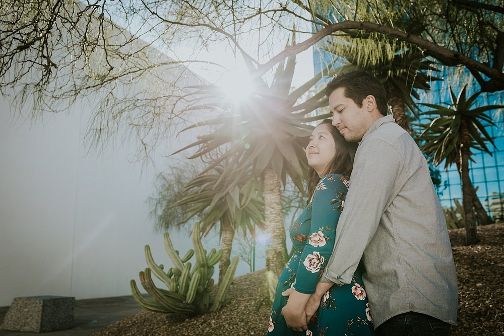 Orange County family photographer. Backlit photo of couple standing together in front of palm tree during maternity photo shoot at Noguchi Garden Costa Mesa