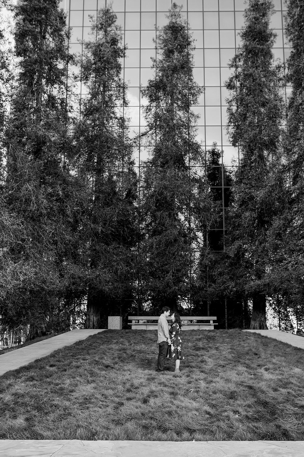 Orange County family photographer. Black and white couple of expecting couple standing in the grass during maternity photo shoot at Noguchi Garden Costa Mesa