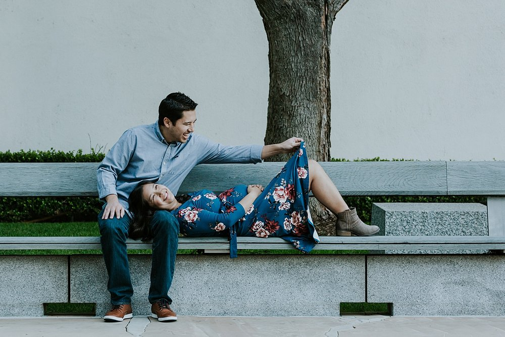 Orange County family photographer. Photo of husband laughing as he fixes moms skirt while sitting on park bench during maternity photo shoot at Noguchi Garden Costa Mesa
