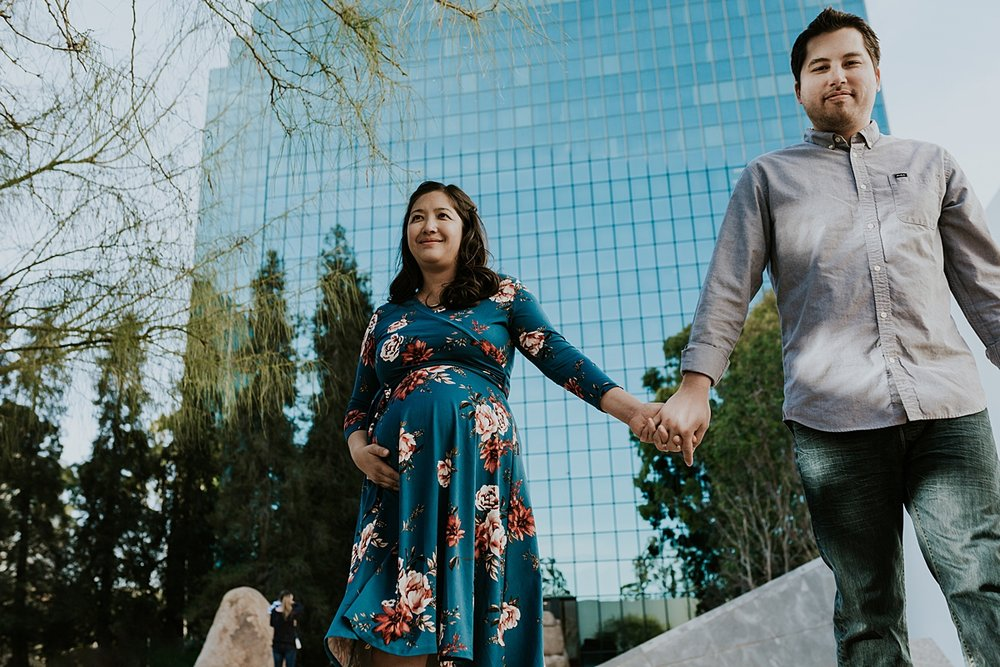 Orange County family photographer. Relaxed candid photo of couple walking hand-in-hand during maternity photo shoot at Noguchi Garden Costa Mesa