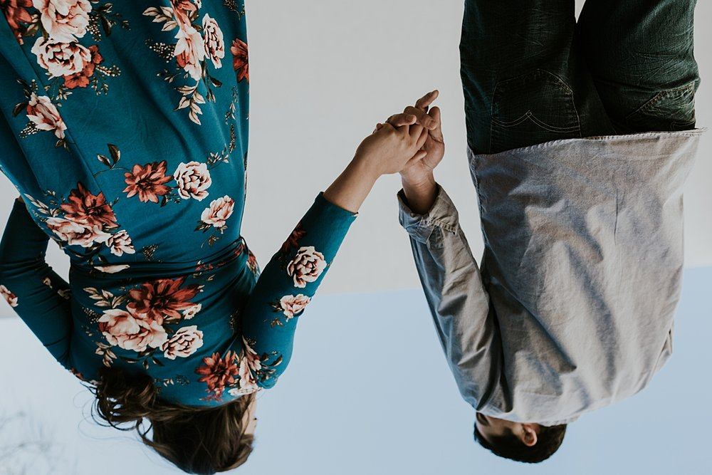 Orange County family photographer. candid photo of expecting couple taken from upside down during maternity photo shoot at Noguchi Garden Costa Mesa