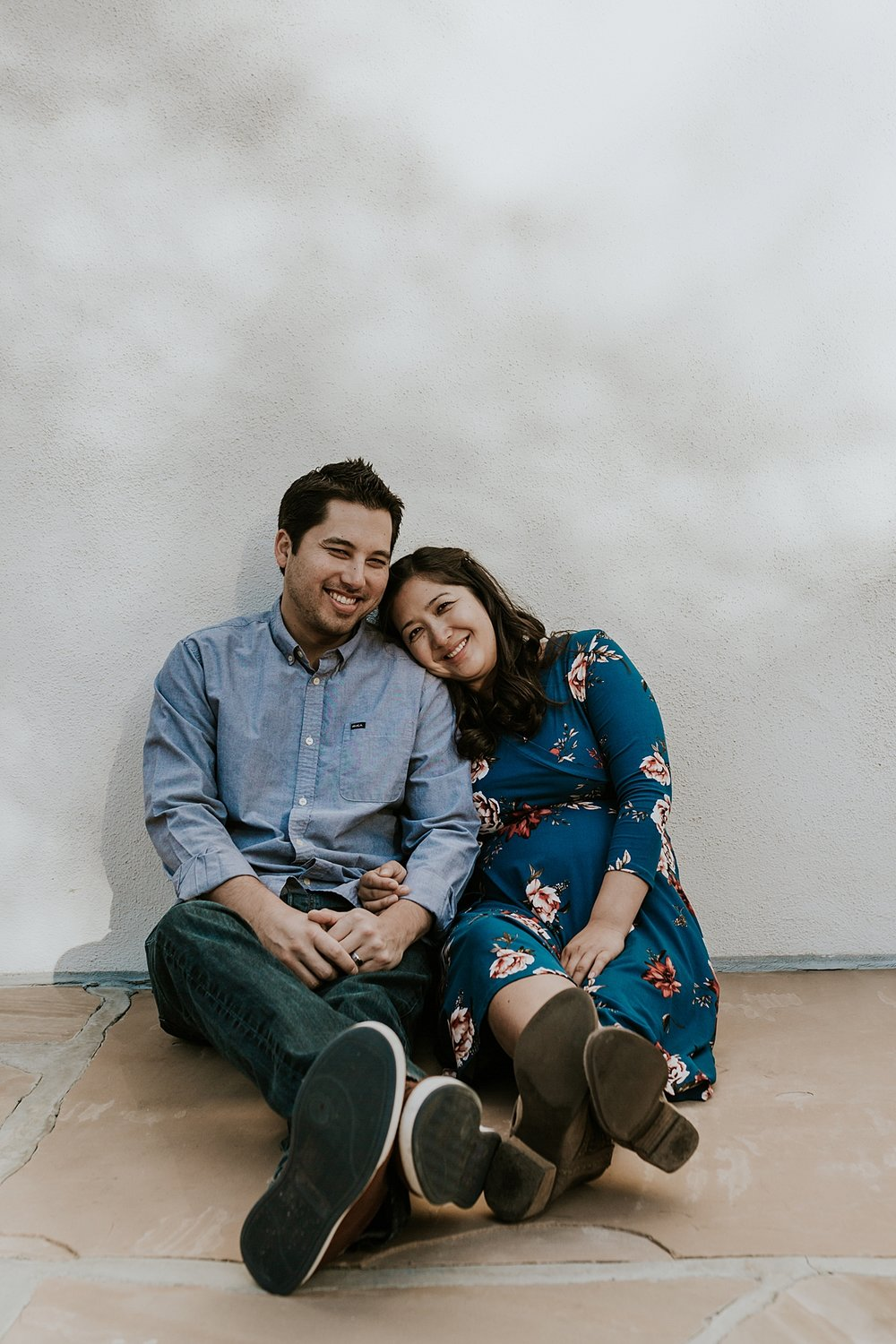 Orange County family photographer. Relaxed candid photo of couple sitting against wall during maternity photo shoot at Noguchi Garden Costa Mesa
