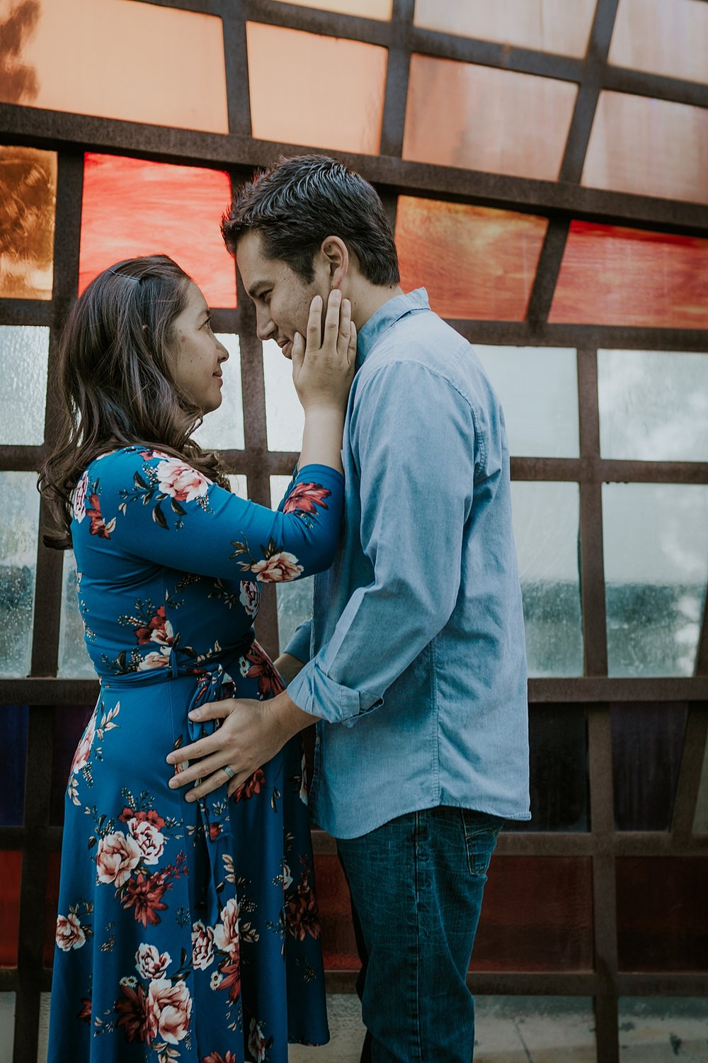 Orange County family photographer. photo of mom to be holding her husband's face in front of colorful glass mural during maternity photo shoot at Noguchi Garden Costa Mesa