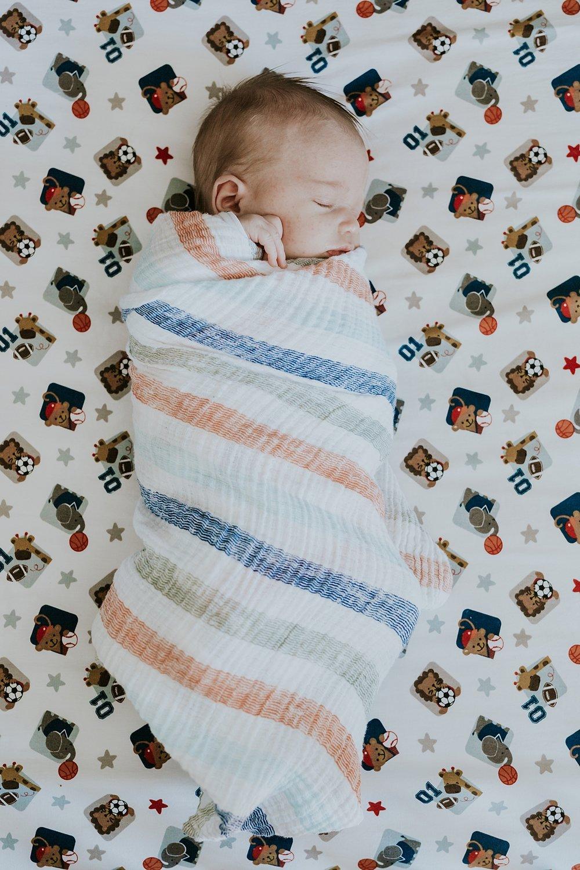 Orange County family photographer. Photo of swaddled newborn  baby boy sleeping in his crib during newborn photo shoot in Mission Viejo Orange County