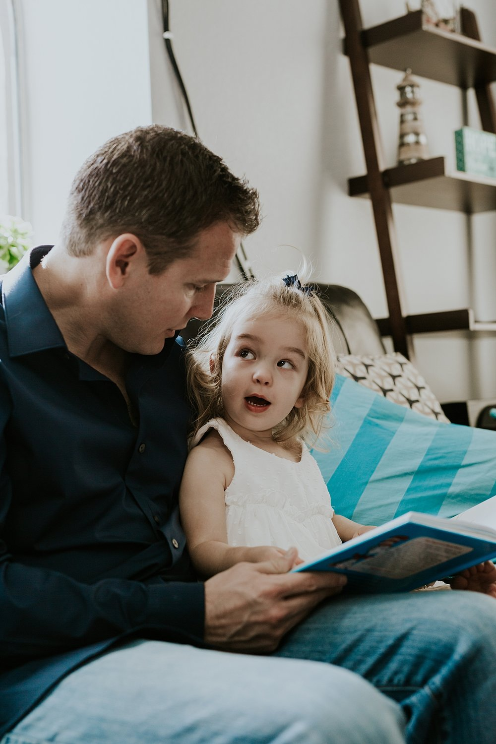 Orange County family photographer. Candid photo of dad and young daughter reading a story during newborn photo shoot in Mission Viejo Orange County