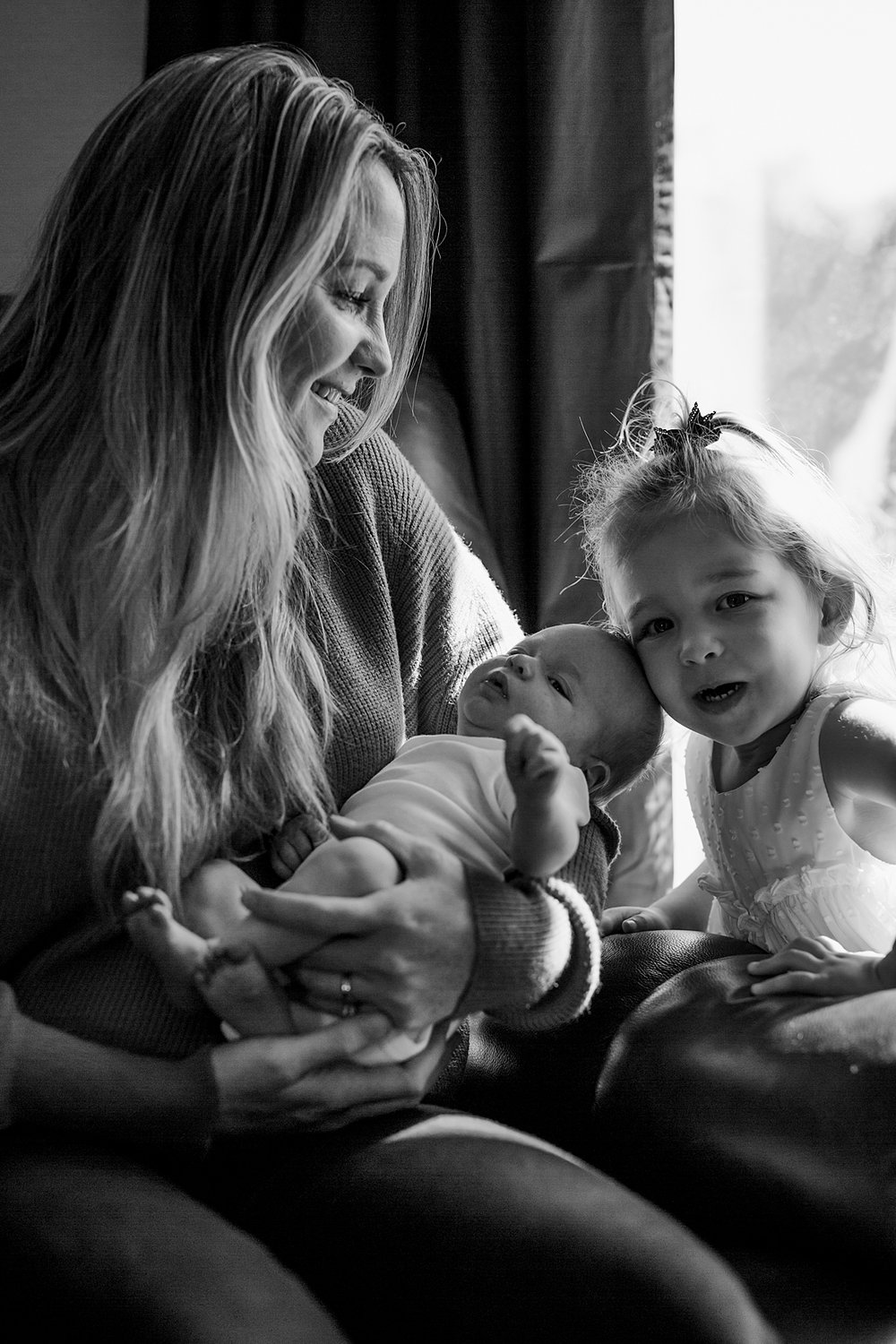 Orange County family photographer. Candid portrait of mom holding newborn son while older daughter comes to say hello during newborn photo shoot in Mission Viejo Orange County