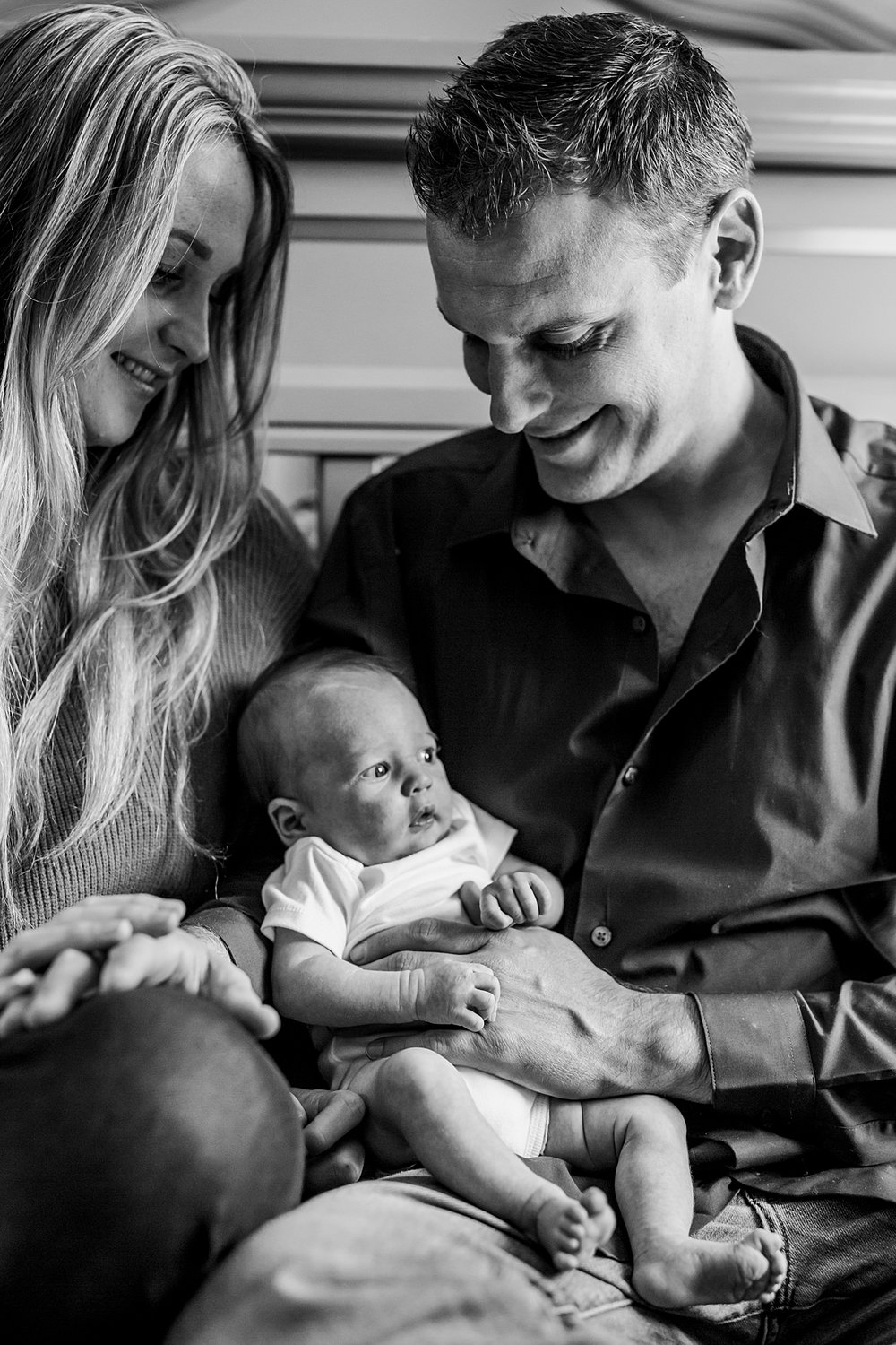 Orange County family photographer. Photo of mom, dad and newborn son taken in baby's room during newborn photo shoot in Mission Viejo Orange County